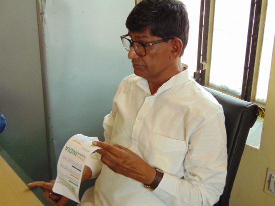 Kalwara Sarpanch going through Kaushalam Foundation's leaflet